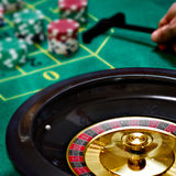 Playing roulette with a moving roulette. With a green table with chips stock photography