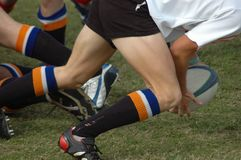 Playing Rugby. White hand and legs of a caucasian rugby player in action catching the ball for his team in a game on the field outdoors in South Africa stock photos