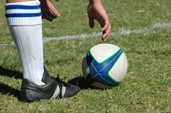 Playing Rugby. A foot and a white hand of a caucasian Rugby player trying to reach the ball for his team in a game outdoors stock photography