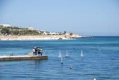 Playing with sailing boats. Marsaskala, Malta - May 31: Group of man sailing mini saling boats from the pier at Marsaskala on May 31, 2014 Royalty Free Stock Images