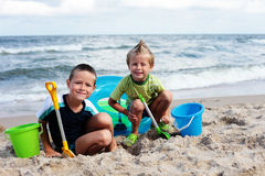 Playing in the sand. Two brothers playing on the beach - kids royalty free stock image