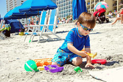 Playing in the sand. A young boy enjoys playing in sand Stock Photos