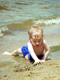 Playing in the Sand. A toddler is playing in the sand at the beach royalty free stock photos
