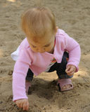 Playing in the Sand. A toddler girl playing in a huge sandbox at the park Stock Image