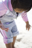 Playing with sand on the beach. Picture of a little girl playing in the sand. Focus is only concentrated on the left hand Stock Photo
