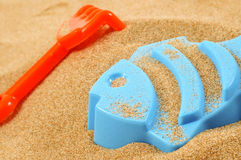 Playing in the sand. A blue fish-shaped mold and an orange toy shovel on the sand Royalty Free Stock Photos