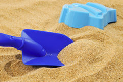 Playing in the sand. Closeup of a blue toy shovel and a blue fish-shaped mold on the sand Royalty Free Stock Photo