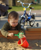 Playing in the sand pit. Young boy is playing outdoor in a sand pit Stock Photos