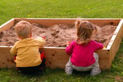 Playing In Sandbox. Two children – two year old twins – play together in a sandbox. Being the best of friends, whatever the one does, the other has to follow
