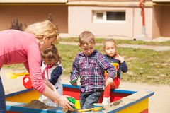 Playing in the sandbox. Children are playing at the playground with sand in the sandbox Royalty Free Stock Photo
