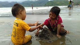 Playing sands in summer beach `Sidem Beach Tulungagung Indonesia`. Little kids having fun with mud and sand in Sidem Beach, Tulungagung Indonesia. Sidem Beach is Royalty Free Stock Photos