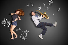 Playing the sax for her. Happy valentines love story concept of a romantic couple against chalk drawings background. Male playing the sax for his girlfriend stock photos