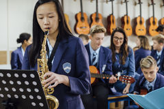 Playing The Saxaphone. Teen student is playing the saxophone in her school music lesson. The rest of the class are in the background, out of focus Stock Photos