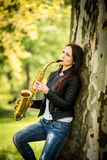Playing saxophone in nature Royalty Free Stock Image