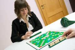 Playing scrabble. Young white caucasian woman plays scrabble at the table royalty free stock photos