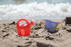 Playing at the seaside. The watering can and bucket on the beach royalty free stock photography