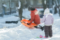 Playing sibling children preparing for winter riding downhill on orange plastic snow slider outdoors Stock Photos