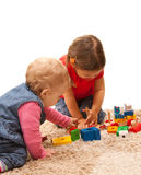 Playing sisters. Sisters playing on the floor with wood toys Royalty Free Stock Photo