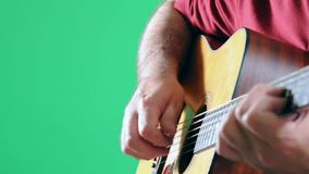 Playing A Six String Acoustci Guitar In Front of A Green Screen. stock footage