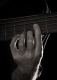 Playing six-string electric bass guitar. Fretting left hand; toned monochrome image Royalty Free Stock Photos