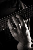 Playing six-string electric bass guitar. Fretting left hand; toned monochrome image Royalty Free Stock Image