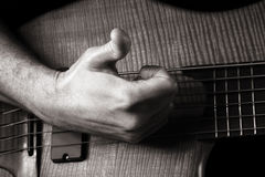 Playing six-string electric bass guitar. Slap technique, right hand; toned monochrome image Stock Image