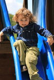 Playing on the slide. Young boy playing in the park on the slide Royalty Free Stock Image