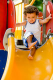 Playing On Slide. A cute young kid playing on a slide in a park royalty free stock image