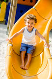 Playing On Slide. A cute young kid playing on a slide in a park Royalty Free Stock Photography