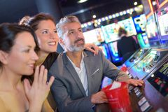 Playing slot machines at casino with girls Stock Images