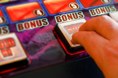 Playing the slots. Gambler playing a gaming machine at the amusement arcade Royalty Free Stock Images