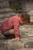 Playing with small stones. Young boy playing with some small stones Stock Image