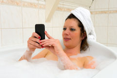 Playing with smartphone in bath Stock Images