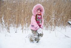 Playing with snow. Little girl playing with snow in a winter woods Royalty Free Stock Image