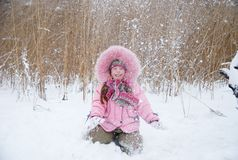 Playing with snow. Little girl playing with snow in a winter woods Stock Photo