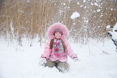 Playing with snow. Little girl playing with snow in a winter woods Royalty Free Stock Photography