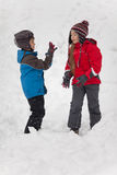 Playing in the snow. Boy throwing a snowball to a girl's face Royalty Free Stock Photos