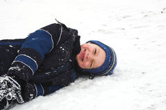 Playing in the snow. A child smiles as he has the time of his life rolling in the snow stock photo