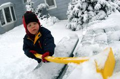 PLAYING IN SNOW. A red-cheeked, three year-old boy clears off a snow-covered picnic table in his backyard while more snow falls Royalty Free Stock Images