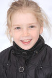 Playing in the snow. Pre teen in a black coat playing in the snow Stock Image
