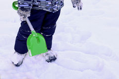 Playing in the snow with a shovel. Royalty Free Stock Photo