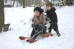 Playing in the snow. Young boy and girl playing on a sledge in the snow Stock Photos
