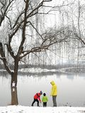 Playing on snowy days. An asia adult in yellow down jacket and two children playing on the park lakeside in the snowing days stock images