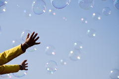 Playing with soap bubbles. Child trying to catch the soap bubbles flying all around Royalty Free Stock Photography