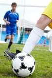 Playing soccer. Photo of soccer ball being kicked by footballer during game Royalty Free Stock Photo