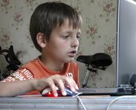 The playing space. The boy playing between favourite toys, viz computer and bicycle Royalty Free Stock Photo