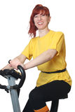 Playing sports on a velosimulator. The young woman goes in for sports on a velosimulator. A white background Royalty Free Stock Images