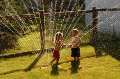Playing In A Sprinkler. A young girl and boy - sister and brother –beat the heat of a hot summer afternoon by playing in a sprinkler Stock Photography