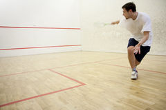 Playing squash. Squash player in action on court Stock Photography