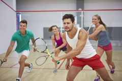 Playing squash with friends. Group of best friends during the squash match Stock Photography